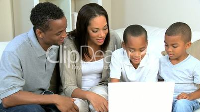 Ethnic Parents Watching Sons Using Laptop