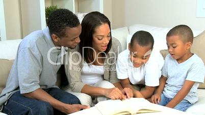Proud Young Parents Listening to their Son Reading