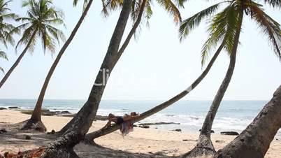 Woman lying on palm tree.