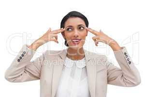 Confident young businesswoman pointing her head with her fingers