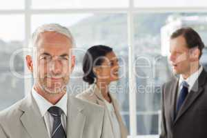 Businessman standing in front of colleagues speaking together