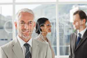 Confident businessman standing in front of colleagues speaking t