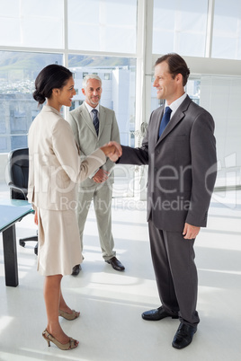 Two people shaking their hands with colleague watching them