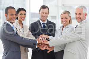 Group of smiling business people piling up their hands together