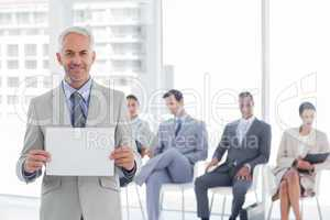 Smiling businessman holding a blank notice