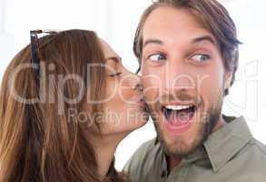Woman kissing man with beard on the cheek
