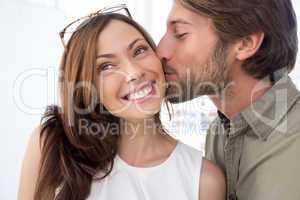 Man kissing pretty woman on the cheek