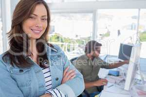 Woman smiling in creative office with arms folded