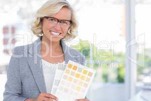Pretty interior designer holding up colour samples