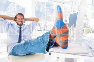 Designer relaxing at desk with no shoes and smiling