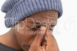 Man in beanie hat wincing with a headache