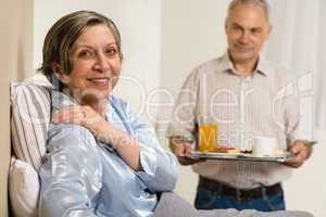 Caring senior man bringing breakfast to wife