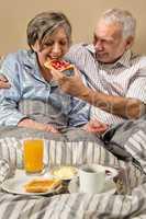 Senior man feeding breakfast to woman