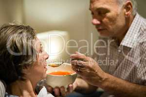 Caring senior man feeding his sick wife