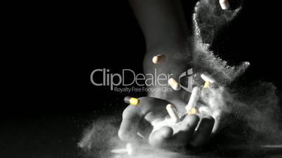 Hand holding pills and white powder dropping dead