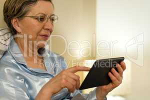 Senior woman using digital tablet in bed
