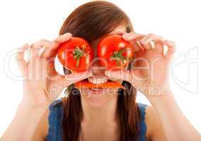 Die junge Frau hält sich zwei Tomaten vor die Augen