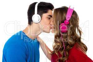 Young couple enjoying music and kissing