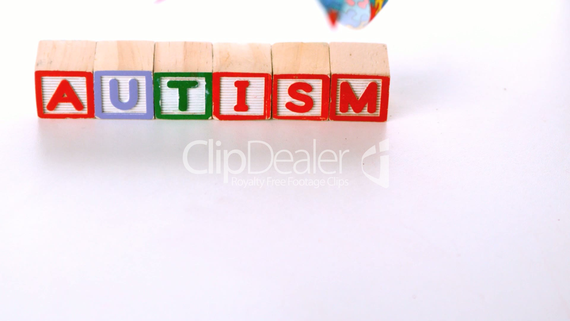 Awareness Ribbon Falling In Front Of Autism Letter Blocks Royalty