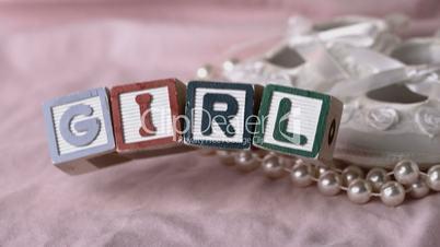 Girl in letter blocks beside booties and pearls on pink blanket