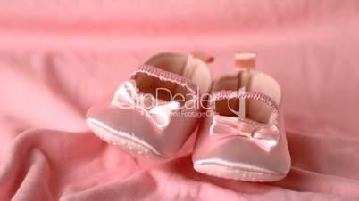 Pink booties falling on pink blanket