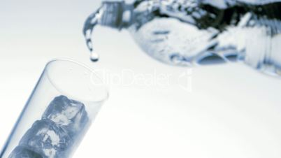 Water pouring into glass with ice low angle view