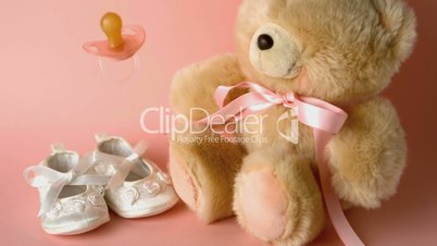 Pink soother falling in front of baby shoes and a teddy bear