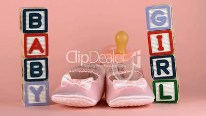 Pink soother falling onto baby shoes besides baby blocks