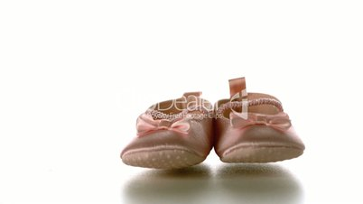 Baby shoes falling and bouncing on white surface