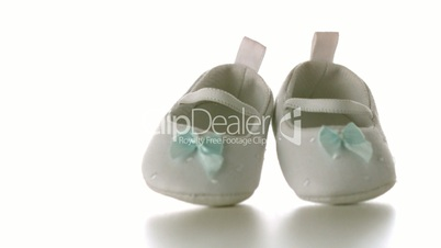 White baby shoes falling on white surface
