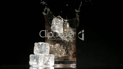 Ice cubes falling into glass of whiskey and ice on black background