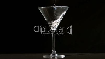 Water pouring into cocktail glass
