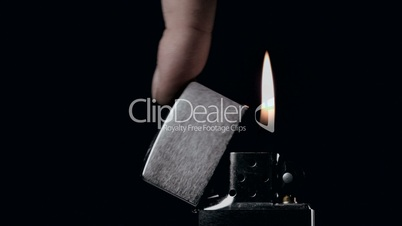Hand closing over retro lighter on flame