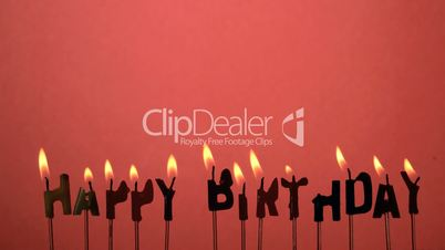 Silhouette of happy birthday candles being extinguished