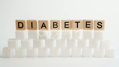 Wall of sugar cubes forming with diabetes letter pieces balancing on top