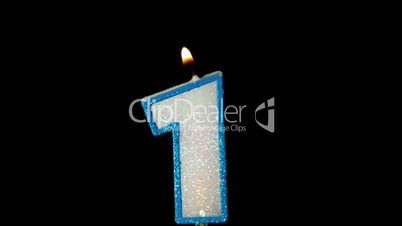 One birthday candle flickering and extinguishing on black background