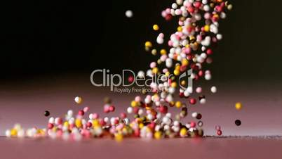 Sprinkles pouring onto pink surface on black background