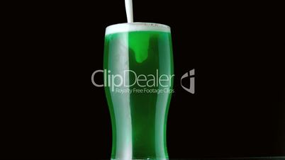 Foam pouring onto pint of green beer on black background