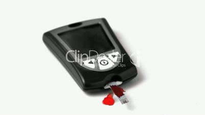 Drop of blood falling onto test strip of blood glucose monitor on white background