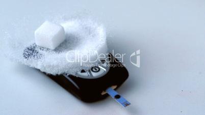 Sugar cube falling onto pile of sugar on blood glucose monitor