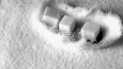 Sugar cubes falling in pile of sugar