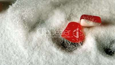 Heart shaped candies falling in pile of sugar