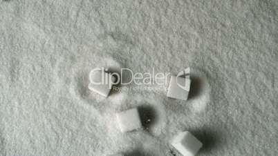Many sugar cubes falling into pile of sugar