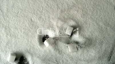 Five sugar cubes falling into pile of sugar