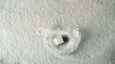Sugar cube falling into pile of sugar