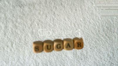 Dice spelling sugar falling into pile of sugar
