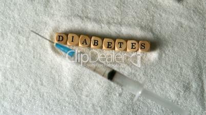 Syringe falling into pile of sugar beside dice spelling diabetes