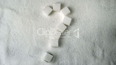 Question mark spelled in sugar cubes forming on pile of sugar