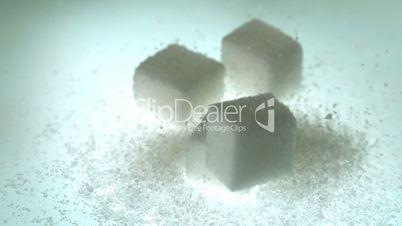 Sugar cube falling onto pile of cubes and powder sugar