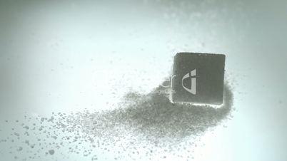 Sugar cube falling onto pile of powdered sugar